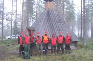 Iloinen metsämiesten joukko kodalla